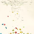 Multi coloured pebbels falling through water with bubbles by kipstar