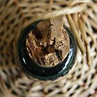 Wine bottle in a basket by MaggieO