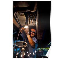 Mechanic soldering a muffler Poster