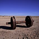 Wheels and axle in the train cemetery near the bigger leading world floors of salt - Salar de Uyuni, Bolivia, South america by Thibaut PETIT-BARA
