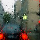 Traffic lights in rain, view through windscreen by Sami Sarkis