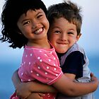 Girl and boy (7-9) embracing, outdoors, smiling, portrait by Sami Sarkis
