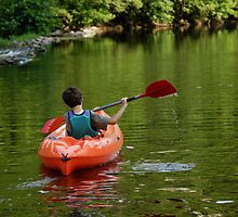 Boy kayaking in river by Sami Sarkis