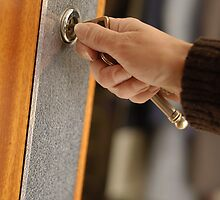 Woman opening front door with key by Sami Sarkis