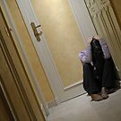 Depressed woman sitting in corridor with head in hands by Sami Sarkis