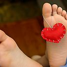 Valentine heart hanging on girl's (6-7) barefeet by Sami Sarkis