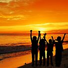Children silhouettes on a  sunset beach by Loredana  Smith