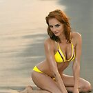 Fashion model in custom design yellow bikini sitting pretty on the sunset beach in Reese Park, NY  by Anton Oparin