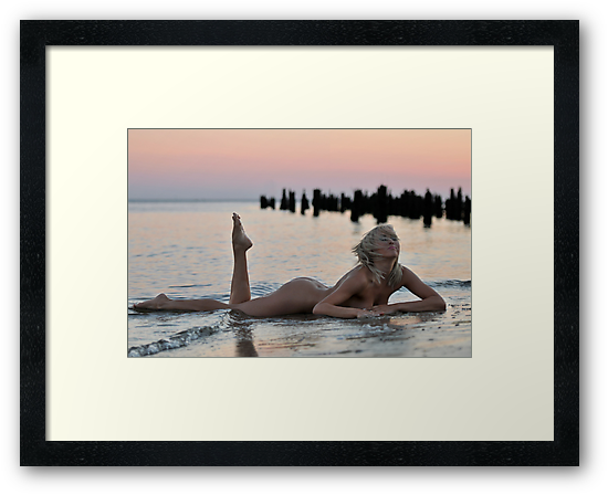Lovely blond naked model lying on sunset beach at dramatic sunset  by Anton Oparin
