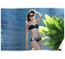 Portrait of a seductive female model in bikini posing in front of blue wall Poster
