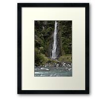 waterfall set amongst mountain and trees Framed Print