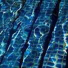 Blue pool tiles with water ripples distorted by the water by Heather  McCann
