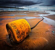 beached yellow mooring buoy by meirionmatthias