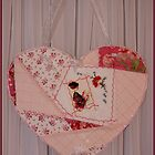 Reading the letter - emboidered patchwork heart. by Sandra Foster