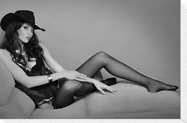Beautiful brunette leggy girl wearing cowboy hat and seductive black lingerie by Anton Oparin
