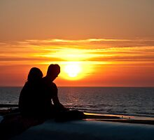 Couple watching the sun set in Villers-sur-Mer, Normandy, France by Michael Brewer