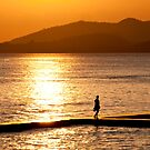 Female figure silhouetted in the setting sun at Puris Bagus in Candidasa, Bali, Indonesia by Michael Brewer