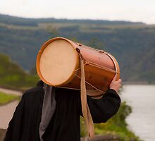 Man in traditional dress carrying a wooden drum along the Rhine River in Southern Germany by Michael Brewer