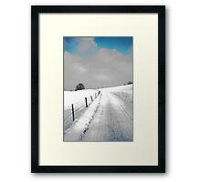 snowy road under a blue sky Framed Print