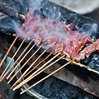 Satays grilling over coals at the market in Amlapura in Bali, Indonesia by Michael Brewer