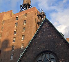 A buildings in New York City and rooftop with old water tower.  by Anton Oparin
