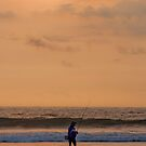 Fisherman in the waves at sunset at Seminyak Beach in Bali, Indonesia by Michael Brewer