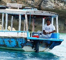 boat pilot fishing off pemateran island by Michael Brewer