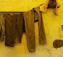 C-156 2011 - Jeans and a sweater drying under a yellow awning by Marjolein Katsma