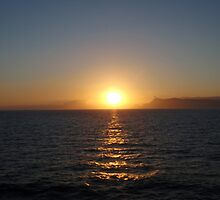 Yellow halo around white setting sun over sea by Grace Johnson