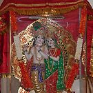 Statue of Lord Krishna and Radha inside a glass case with a cloth cover by ashishagarwal74
