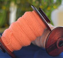 Spinning wheel bobbins orange yarn by Carlo Marandola