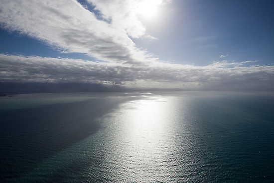 Aerial view of sea near Queensland, Australia with white cloud formations and blue ocean by Sharpeyeimages