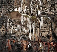 melting cascade of icicles on a cliff face by morrbyte