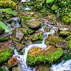 Stream flowing over rocks by Heike Richter