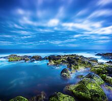 Dusk over calm blue sea over ocean and cloudy sky in Port Fairy, Victoria, Australia by hangingpixels
