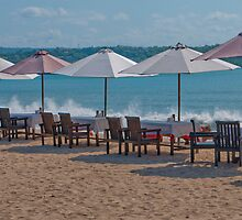 Tables, chairs and umbrellas lining the surf at Jimbaran Beach, Bali, Indonesia by Michael Brewer