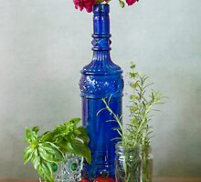 Blue glass bottle with vegetables and flowers by Luisa Fumi