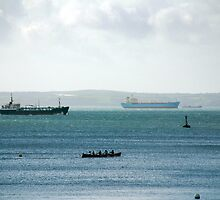Silhouette of Gig boat racers with large cargo ships in background, St Mawes, Cornwall by silverportpics