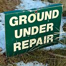 ground under repair sign on snow covered links golf course by morrbyte