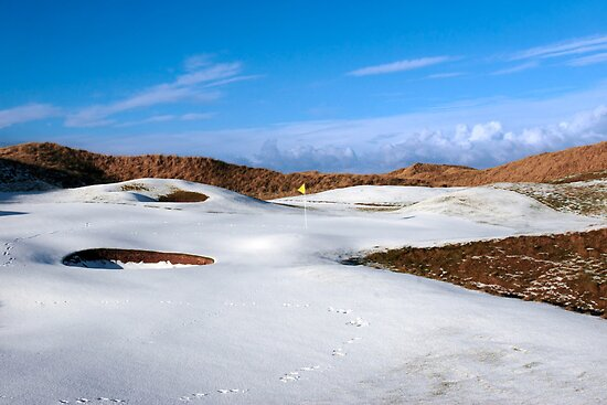 snowy covered links golf course with yellow flag by morrbyte