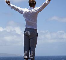 Man on a Bluff above the ocean celebrating life by DeborahKolb