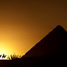 Four camel riders silhouetted at sunset near a pyramid in Egypt by Michael Brewer