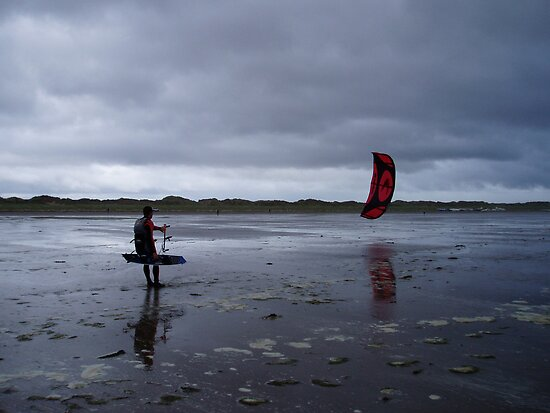 Atlantic storm approaches man with hand glider on Inch Beach. by Grace Johnson