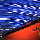 Galaxy Star Trails Pass Over Red Cabin Roof by Gavin Heffernan