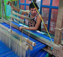 young man working a hand loom- El Salvador by David Chesluk