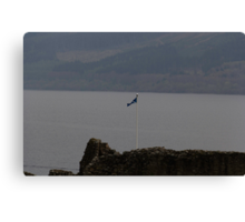 Scottish flag flying high over the remains of Urquhart Castle  Canvas Print