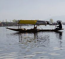 Kashmiri man rowing a shikara without tourists by ashishagarwal74