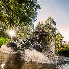 Quad rider through water stream by homydesign