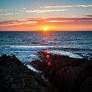 the sun sets in the middle of lundy island by James Calvey
