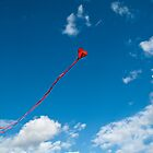 Flying red heart - shaped kyte on a clear blue sky by Reinvention